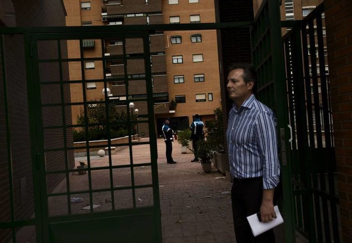 Un vecino de Teresa Romero, la enfermera española infectada con ébola, se encuentra cerca de la entrada al complejo de apartamentos donde reside, custodiado por un par de policías locales, en Alcorcón, cerca de Madrid, España. (Agencias)
