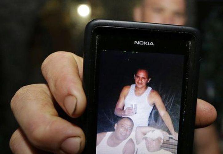 Aliandi García muestra en su teléfono el 9 de octubre del 2014 una foto de su tio José Ramón Acosta (parado), quien falleció tratando de llegar en balsa desde Cuba a Estados Unidos. (Agencias)