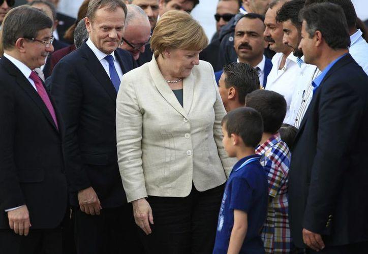 La canciller alemana, Angela Merkel, acompañada por el primer ministro de Turquía, Ahmet Davutoglu (izq), habla con los refugiados durante su visita al campo de refugiados Nizip en la provincia de Gaziantep, en el sureste de Turquía. (Agencias)