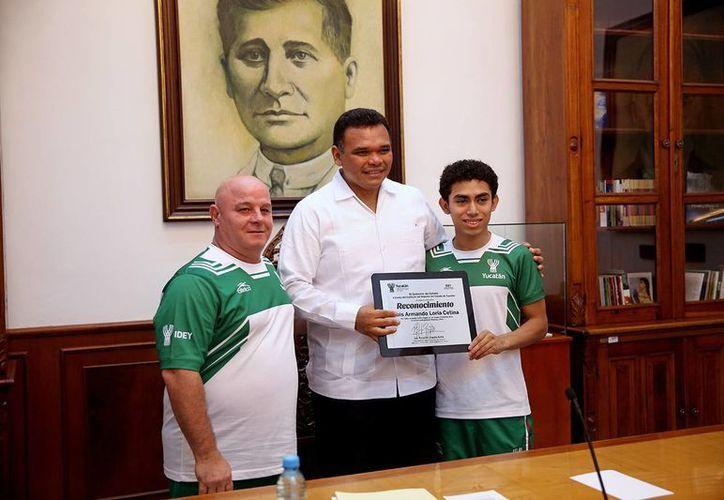 El gobernador Rolando Zapata entrega un reconocimiento al gimnasta Luis Loría Cetina en presencia de su entrenador, José Luis Nuñez García. (Milenio Novedades)