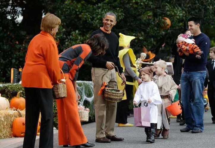 El presidente Barack Obama y su esposa Michelle departieron con niños disfrazados. (AP)