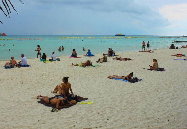 Los turistas no dejaron de disfrutar de la playa a pesar de las lluvias intermitentes y del cielo nublado. (Daniel Pacheco/SIPSE)