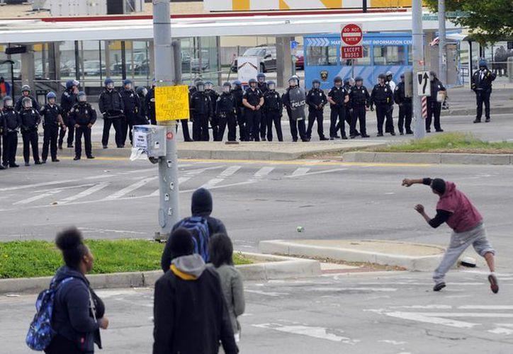 Manifestantes lanzan objetos a los miembros del Departamento de Policía de Baltimore durante los disturbios posteriores al funeral de Freddie Gray en Baltimore.  (Lloyd Fox/El Sol de Baltimore a través de AP)