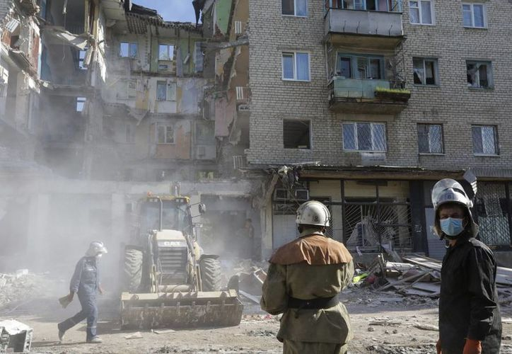 Rescatistas en un edificio en el que se produjo una explosión de gas tras el lanzamiento de un proyectil, durante los enfrentamientos ntre las fuerzas gubernamentales y los separatistas prorrusos en Nikolaevka, cerca de Slaviansk. (EFE)