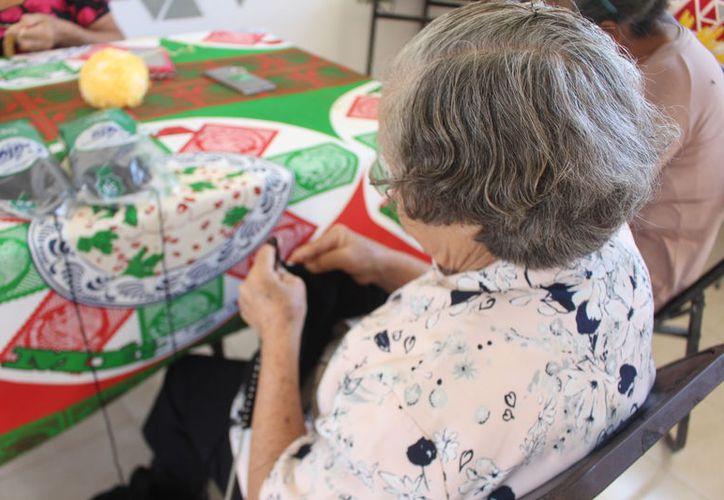 El Inapam promueve actividades de manualidades para que los abuelitos inviertan su tiempo y pasen un rato agradable. (Jesús Caamal/SIPSE)