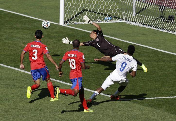 El inglés Daniel Sturridge intenta un tiro a gol enmedio de la marca de los costarricenses Roy Miller y Giancarlo Gonzalez  (Foto: AP)