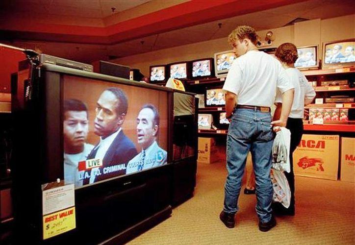 En esta foto del 20 de junio de 1994, clientes en un centro comercial en Tampa, Florida, siguen el juicio de O.J. Simpson, transmitido en vivo desde Los Angeles, en los televisores de una tienda. (Agencias)