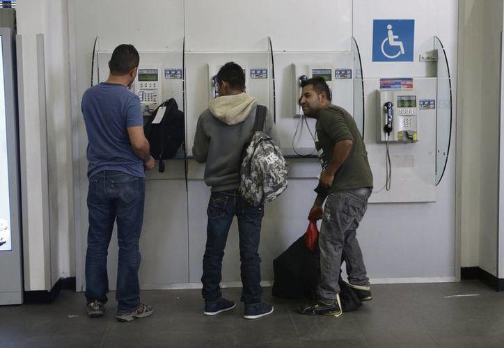 Mexicanos deportados de Estados Unidos hablan por teléfono en el Aeropuerto de la Ciudad de México, el 23 de febrero de 2017. El Politécnico lanzó un programa para revalidar estudios a connacionales repatriados del vecino país. (AP/Marco Ugarte)