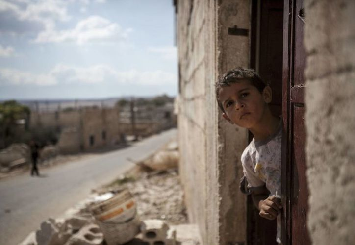 Un niño sirio de Idlib apenas saca la cabeza de su casa mientras fuerzas del régimen y rebeldes combaten. (Agencias)