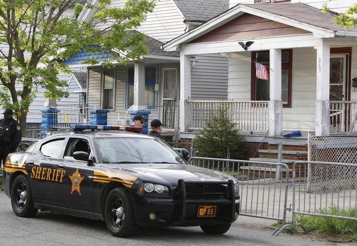 Policías permanecen frente a la casa de la Avenida Seymour donde estaban las mujeres secuestradas. (EFE)